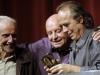 Abrazando al escultor uruguayo Octavio Podesta y al trovador español Joan Manuel Serrat, 2010.   Foto La Nación