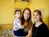 En brazos de su hermana menor, Carly, junto a la hermana mayor Caitlin.