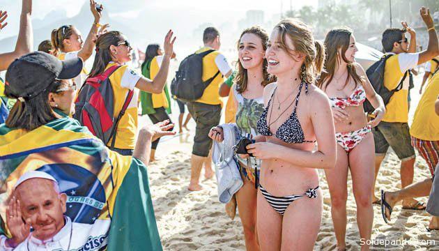 Jóvenes de Río de Janeiro, atravesando una playa de la ciudad carioca rumbo al encuenrtro con el Ppapa Francisco, quien llegó aquí el lunes. | Foto AFP