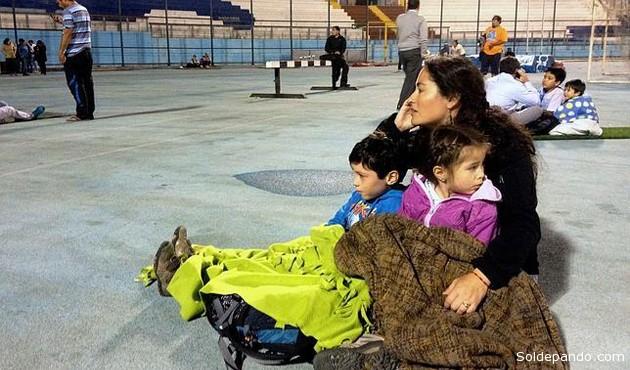 Familias refugiados en un campo deportivo en el norte de Chile. El uso de celulares permitió una organización eficiente de casi un millón de evacuados hacia las zonas altas. | Foto AFP
