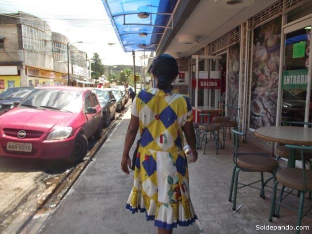 LA TRAMPA DEL MUNDIAL DE FÚTBOL En la fotos, una joven indígena Warao deambulando en Santa Elena, la capital del municipio Gran Sabana y la última ciudad venezolana de cara al Brasil, que se encuentra al menos a 1.400 kilómetros de Caracas y a 870 Kilómetros de Manaus, la sede Amazónica del Mundial Brasil 2014.  Gran Sabana es el territorio del pueblo pemón. La localidad, de alrededor de 20 000 habitantes, es lugar de compras para buena parte de  los más de tres millones de personas que habitan entre Boa Vista y Manaus, las dos ciudades brasileras en el extremo fronterizo con Venezuela. Al cambio, cualquier precio les resulta irrisorio. Y, desde que arrancó el mundial, cientos de venezolanos y extranjeros cruzan la Gran Sabana ansiosos por llegar al Arena Amazonia.  Las mujeres warao y sus niños bajaron en el Terminal Internacional de Santa Elena de Uairén apenas con lo puesto, sin abrigos, sin cobijas, sin zapatos, sin equipajes. Ellas con vestidos hechos a la medida, estampados en flores, líneas o cuadros, con las faldas sobre la rodilla y mangas a un cuarto. Los pequeños con franelas y pantalones cortados a media pierna. Los waraos son los habitantes de Mariusa, la región del estado Delta Amacuro sobre la cual se extiende el Parque Nacional Delta del Orinoco. Su hogar es una isla entre los caños Macareo y Mariusa, justo en el punto medio de la desembocadura del Orinoco. Viven de la pesca, de la recolección, del turismo y de la artesanía que usan y venden. En Santa Elena, las mujeres y los niños warao mendigan con envases que antes contuvieron jugo, arroz chino, crema de arroz. Sin mediar palabras, pues sólo hablan su lengua autóctona, acercan sus potes a los lugareños, a los brasileros, a los turistas, a los viajeros que, por estos días, apenas pisan Santa Elena rumbo a Manaus, al Estadio Arena Amazonia. (Datos de Morelia Morillo)