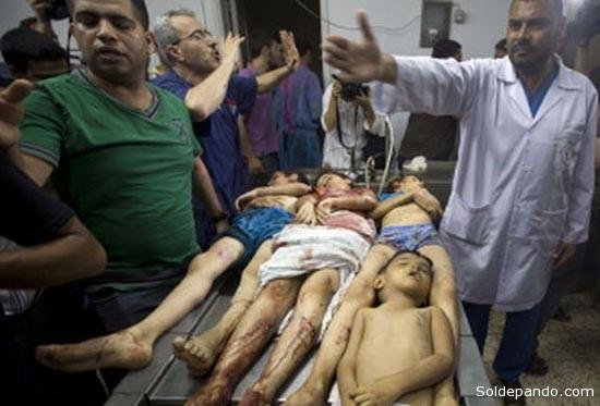 UN ATROZ DAÑO COLATERAL DE LA GUERRA EN GAZA Médicos palestinos del hospital Al Shifa, en Gaza, muestran los cadáveres de tres niños de la familia Shuheiber, muertos en un ataque israelí .   Foto AFP