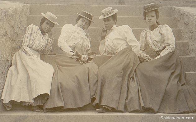 Cuatro mujeres afroamericanas sentadas sobre las gradas del edificio de la Universidad de Atlanta, en Georgia, a principios del siglo XX. En la proporción media de ascendencia africana dentro el territorio norteamericano, los afroamericanos en Georgia y Carolina del Sur tienen el porcentaje más alto promedio de genes africanos.   Foto Biblioteca del Congreso de los Estados Unidos