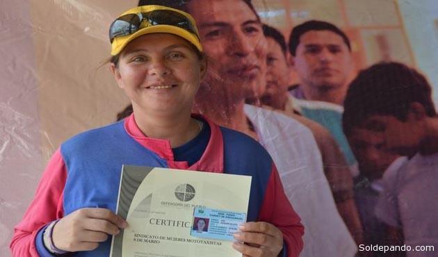 La primera afiliada del nuevo Seguro con su certificado de registro y su carnet de asegurada.   Foto GADP