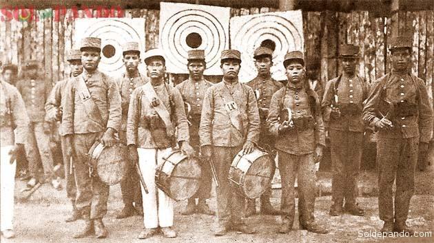 """¿VESTÍAN UNIFORME MILITAR LOS INDÍGENAS FLECHEROS? Obtuvimos esta foto en la ciudad de Cobija. Nos la entregó un oficial del Regimiento Riosinho afirmando que se trata de una tropa perteneciente a la Columna Porvenir que durante la Guerra del Acre estuvo al mando del entonces capitán Federico Román. No pudimos confirmar su autenticidad; aunque la imagen habla por sí sola. Son indígenas reclutados por el Ejército de Bolivia en la región amazónica, el uniforme militar que llevan es característico de principios del siglo XX, el ambiente es el de una barraca cauchera y, por lo que se ve, integraban una banda marcial como cornetas y tambores. Lo llamativo son los paneles al fondo que sirven para practicar tiro al blanco con arcos y flechas. Son, sin duda, indígenas flecheros. Se sabe que la Columna Porvenir estaba integrada por siringueros y civiles al servicio del empresario cauchero Nicolás Suárez, operaban como una guerrilla; pero también es sabido que el capitán Federico Román impuso un mando de disciplina castrense que habría sido una de las causas de su posterior controversia con Suárez. Tras la guerra Román publicó sus conferencias en las que acusaba al cauchero de """"mezquino"""" y Suárez respondió al militar publicando documentos reservados que describían la estructura de la Columna Porvenir.   Foto Sol de Pando"""