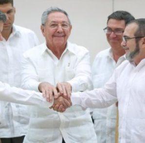 El presidente de Colombia, Juan Manuel Santos, se da la mano con el jefe de las FARC, Rodrigo Londoño 'Timochenko', en presencia del presidente de Cuba, Raúl Castro.   Foto Reuters